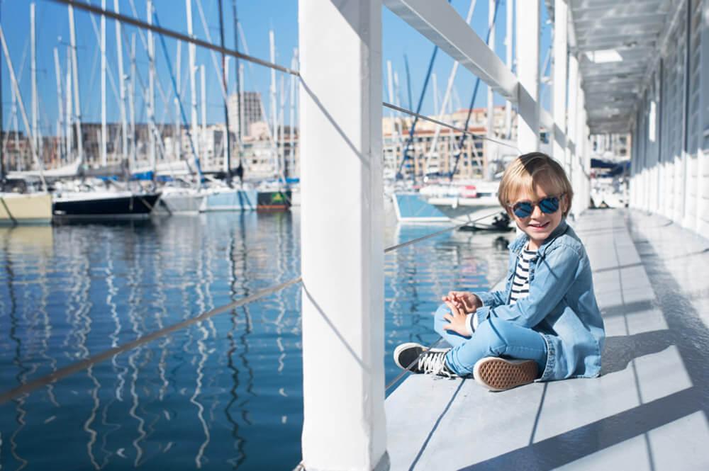 Portrait d'un enfant modèle avec uns superbe casquette Vans. Photo devant les voiliers du vieux-port à Marseille.
