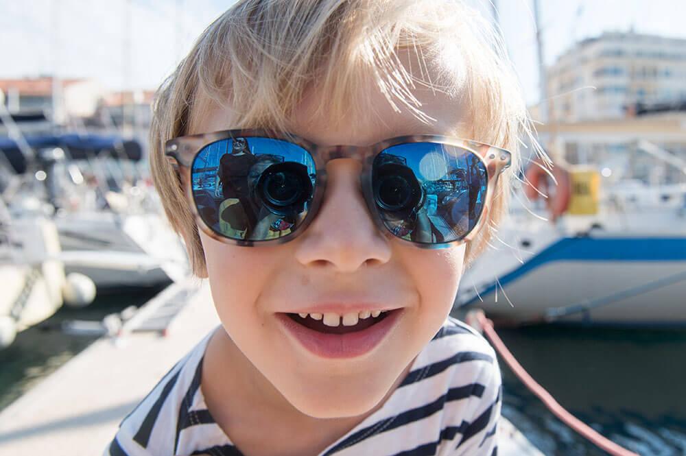 Portrait rapproché d'un enfant blond avec de grandes lunettes.