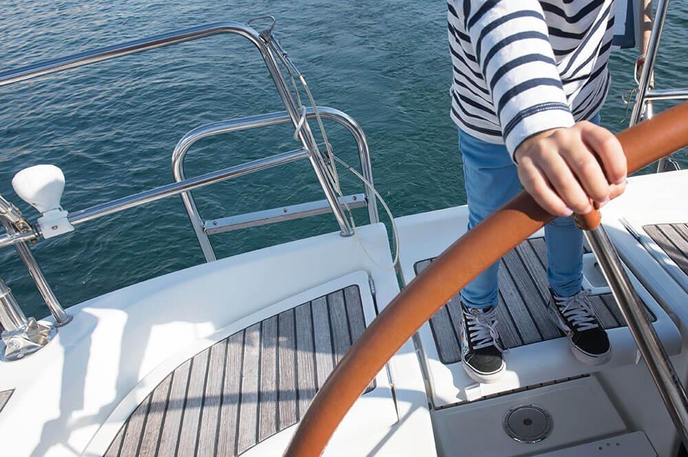 Enfant à la barre d'un voilier.