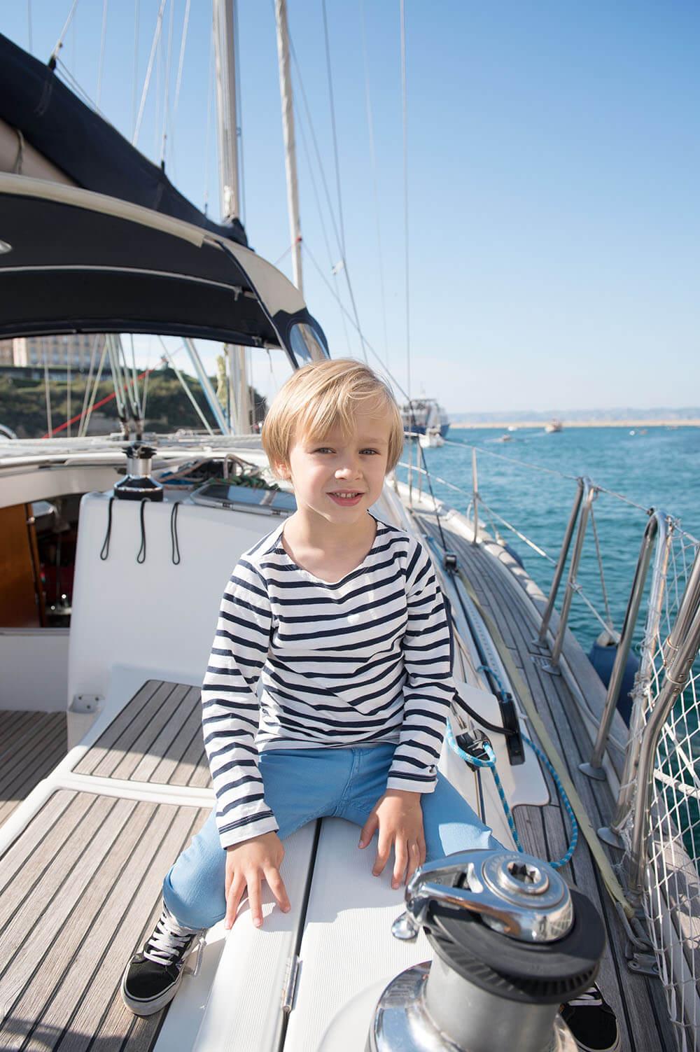 Jeune homme à califourchon sur le rebord de son voilier.