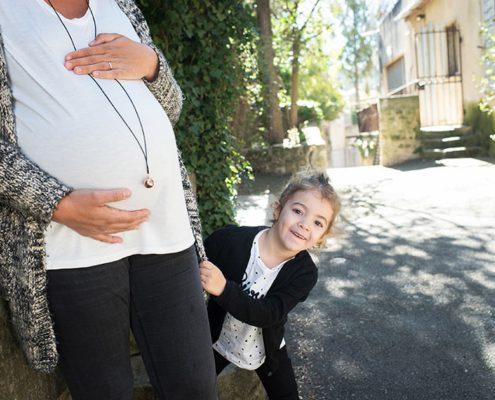 Enfant se cachant derrière le gros ventre de sa maman enceinte.