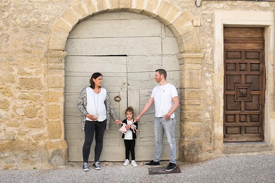 Portrait en famille devant une ancienne porte verte.