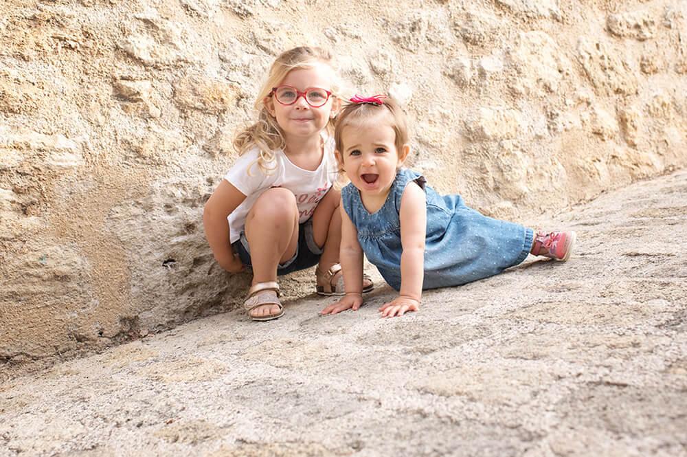 Portrait de deux sœurs assises par terre.