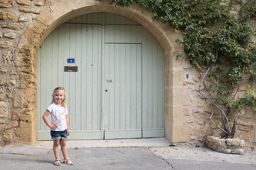 Séance photo famille Luberon. Demoiselle posant devant une jolie porte verte.