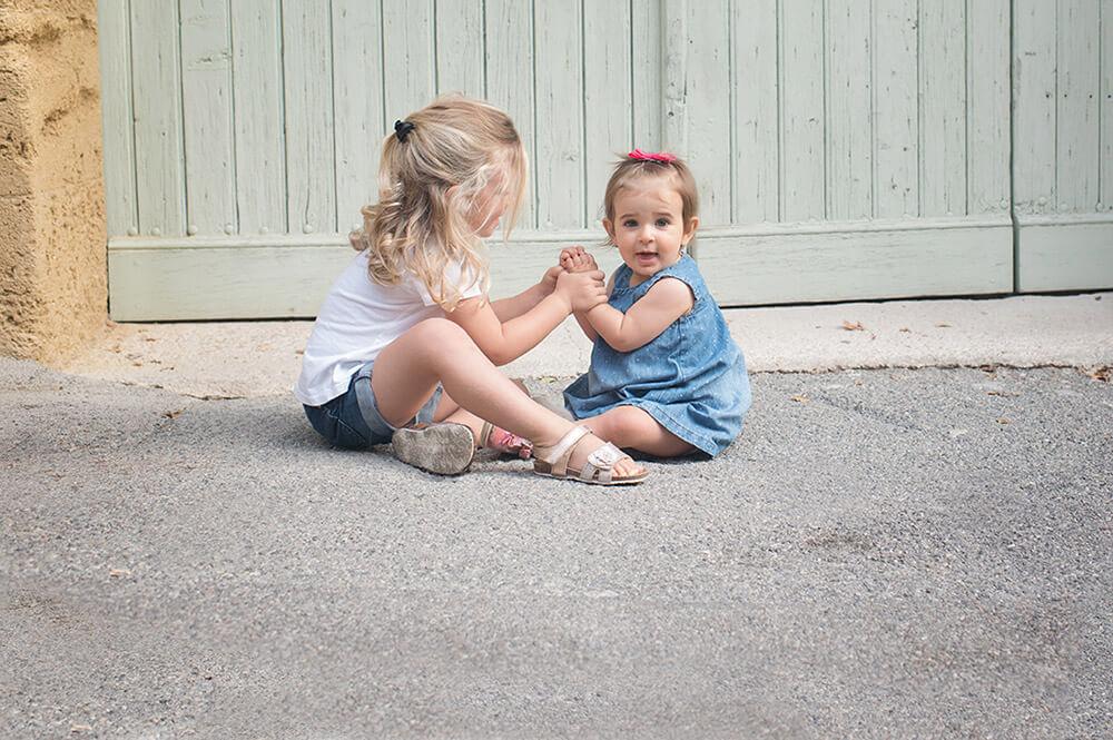 Deux sœurs assises par terre et jouant à se taper dans les mains.
