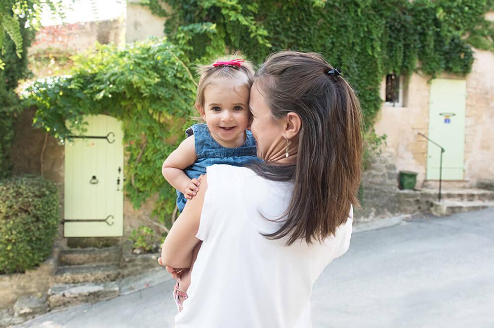 Portrait enfant dans les bras de sa mère devant une jolie façade de maison.