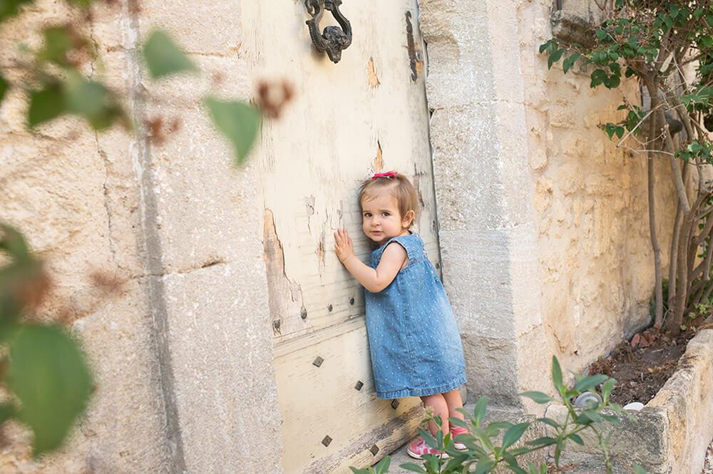 Enfant de un an se tenant debout devant une porte ancienne.