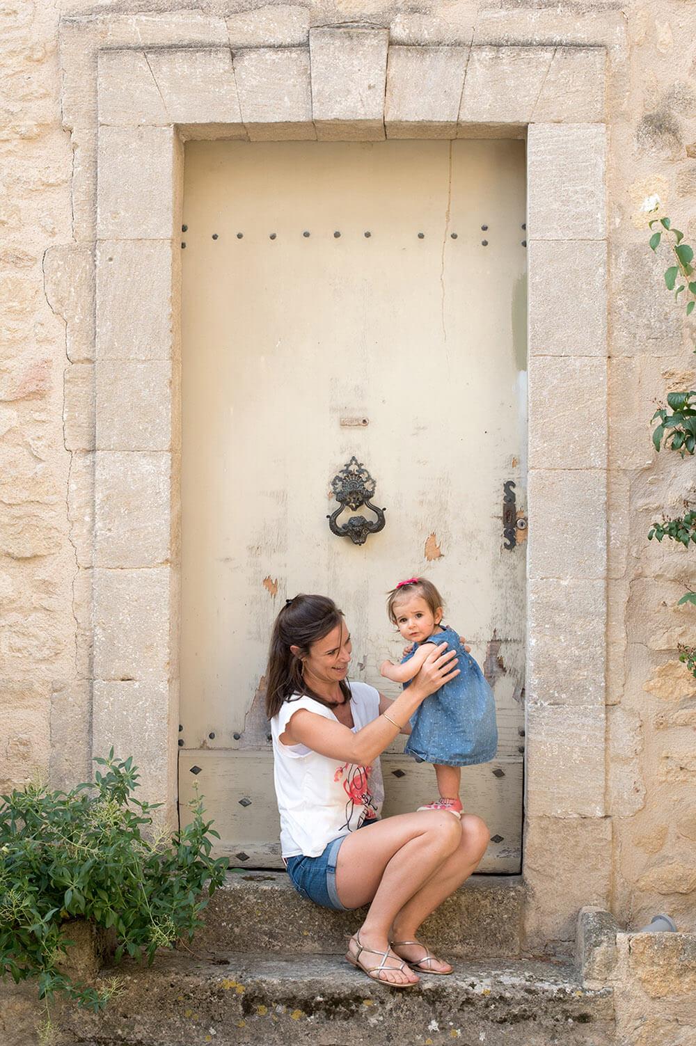 Portrait d'une maman et sa fille de un an devant une jolie porte ancienne.