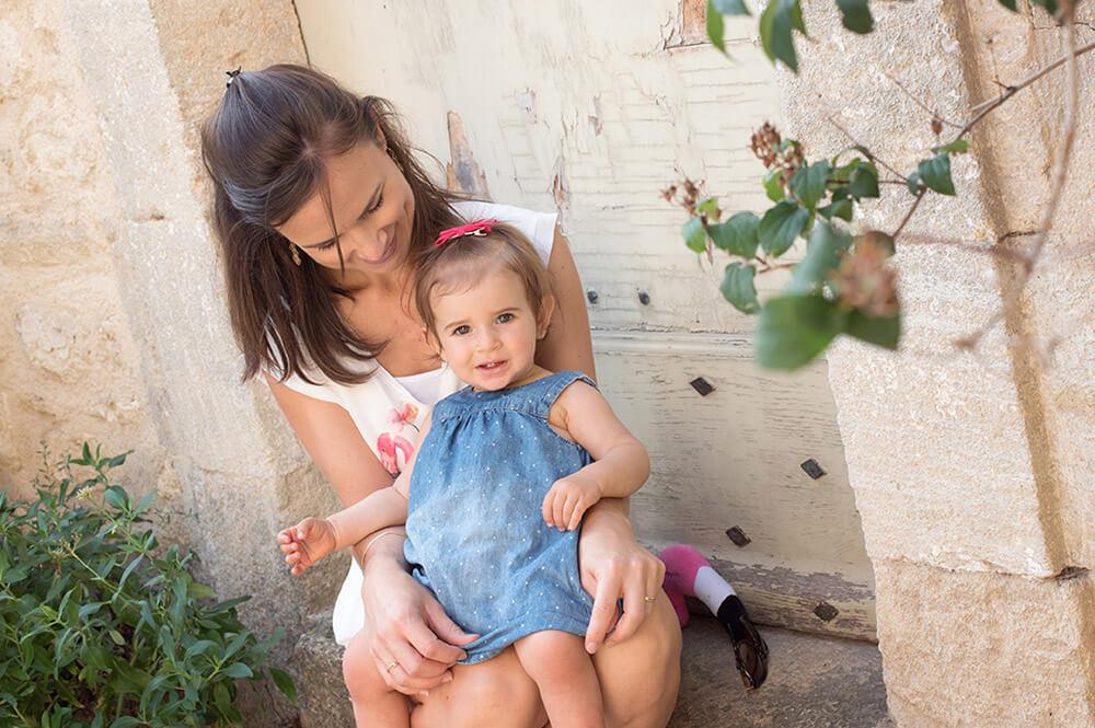 Séance photo famille Luberon. Portrait lifestyle Luberon. Portrait mère-fille assises devant une jolie porte en bois.