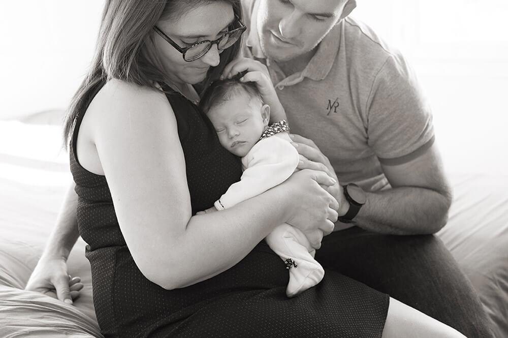 Portrait de jeunes parents avec son nouveau-né. portrait serré en noir et blanc.