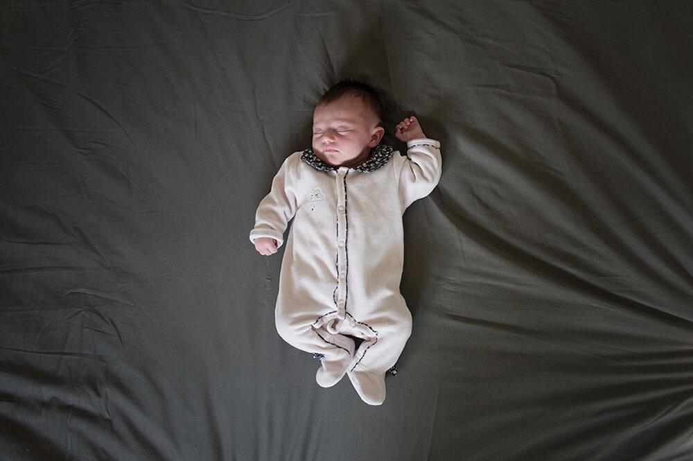 Séance nouveau-né Marseille. Seul allongé sur le lit.
