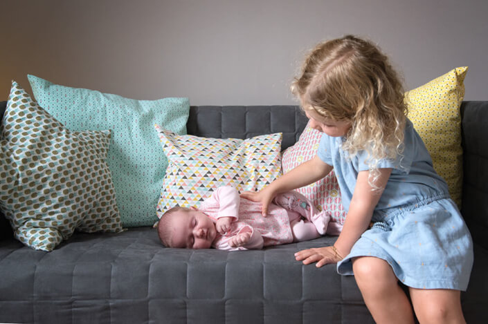 Portrait de la grande sœur regardant tendrement sa toute petite sœur.