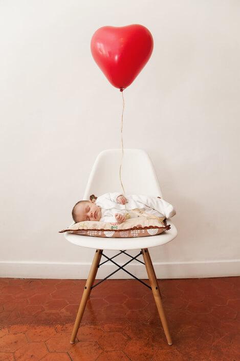 Portrait original d'un nouveau-né tenant un ballon hélium en forme de cœur.