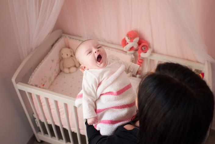 Portfolio bébé naissance Marseille. Maman va coucher son bébé fatigué.