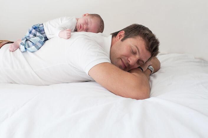 Papa et son bébé dormant tous les deux à plat ventre sur le lit.