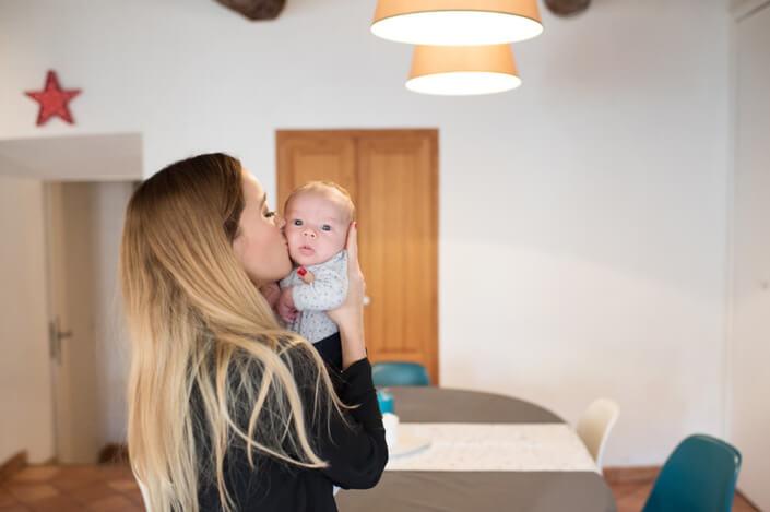 Bisou tendre de maman sur la joue de son tout-petit.