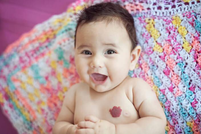 Portrait de bébé souriant sur sa jolie couverture très colorée.