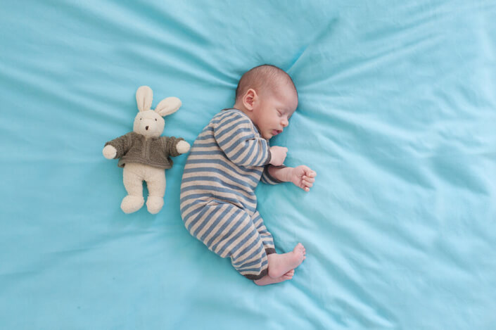 Chacun son côté. Photo rigolote de bébé et son petit doudou lapin.