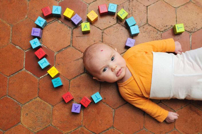 Portrait d'un bébé avec ses cubes en bois colorés.
