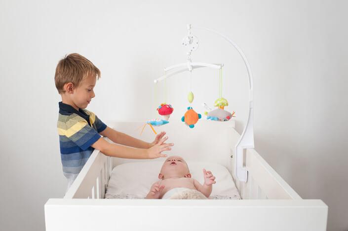 Portfolio bébé naissance Marseille. Bébé dans son lit et jouant avec son mobile.