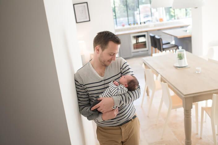 Jeune papa entrain d'admirer son bébé.