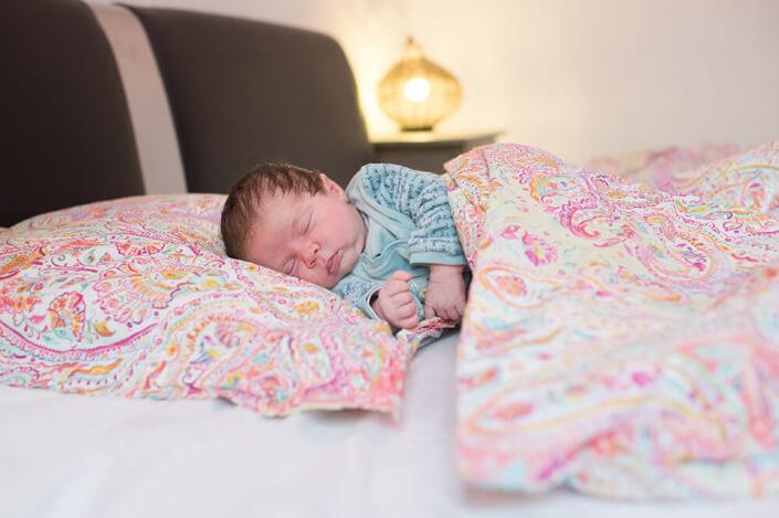 Portfolio bébé naissance Marseille. Bébé dormant sous la couette des parents.