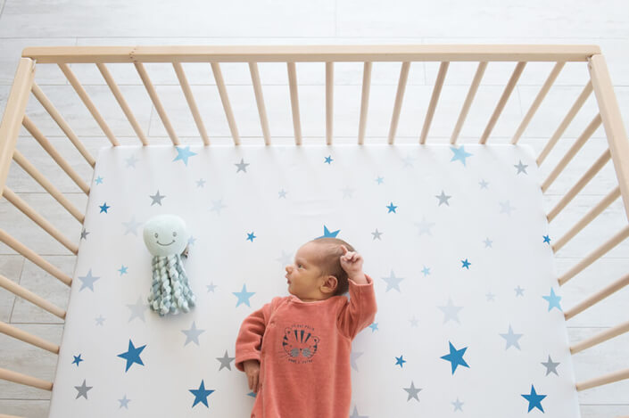 Portfolio bébé naissance Marseille. Bébé parlant avec son doudou pieuvre.