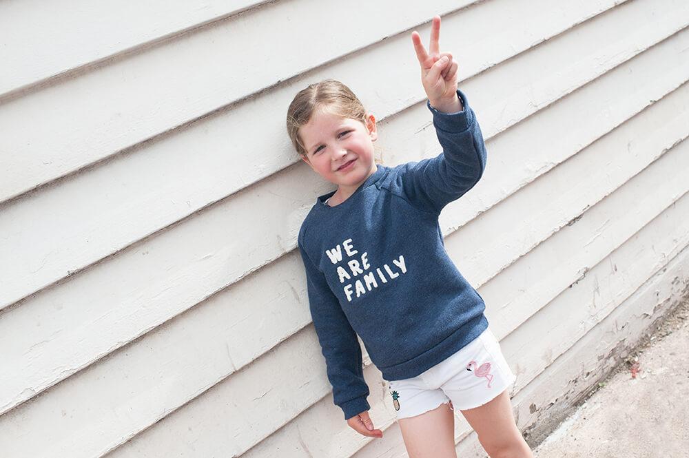 Portrait d'une jeune fille avec un pull We are family.