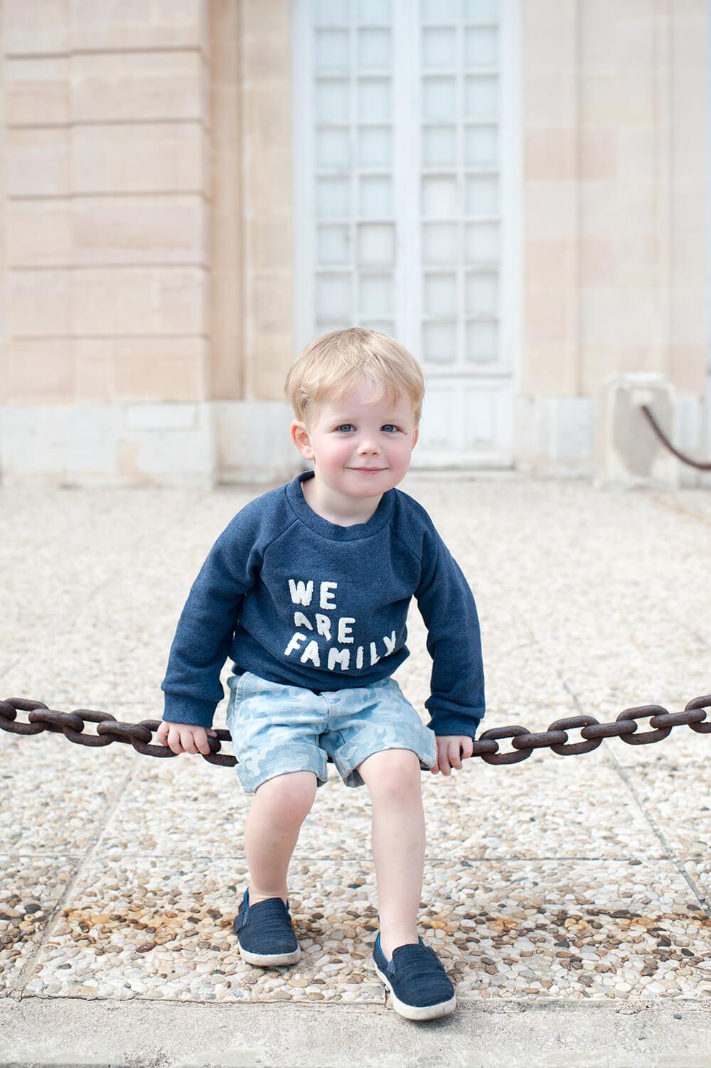 Blondinet jouant à se balancer sur une chaine.