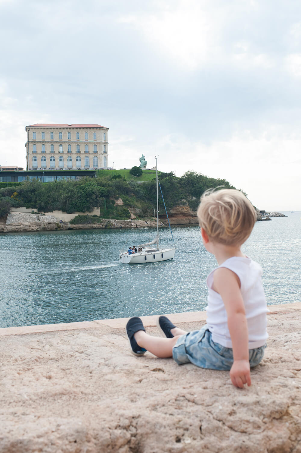 Garçonnet regardant les bateaux passés.