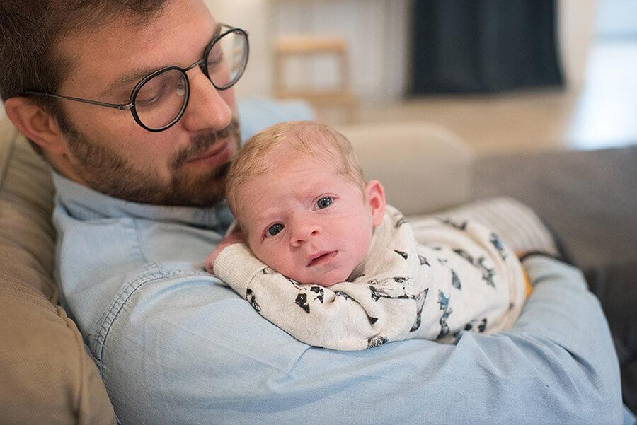 Portrait d'un nourrisson dans les bras de son papa.