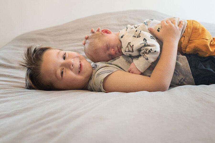 Photo d'un nouveau-né sur le torse de son grand frère.
