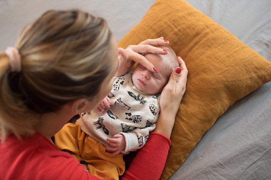 Caresse sur le visage de son nouveau-né.