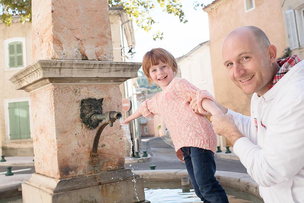 Portrait rigolo d'une jeune fille autour d'une fontaine.