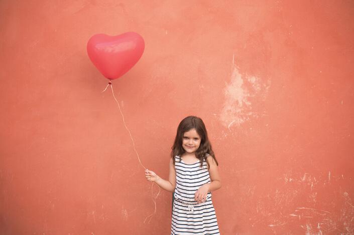 Demoiselle tenant un ballon hélium cœur rouge