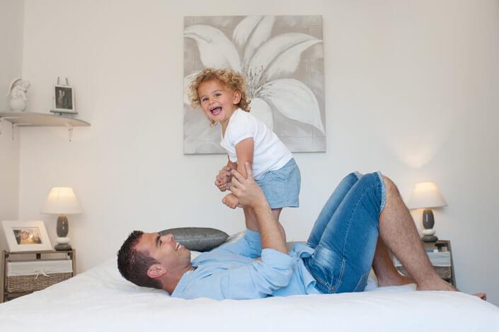 Enfant sautant sur le ventre de son père.