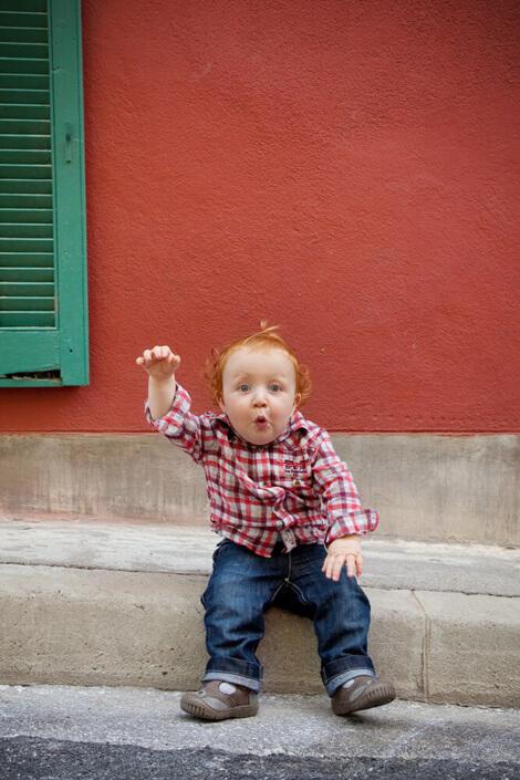Petit enfant rouquin devant un mur rouge et un volet vert. Portrait coloré.