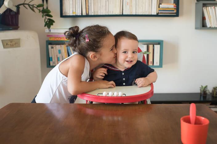 Bébé assis dans sa chaise haute se faisant faire un bisous par sa grande sœur.