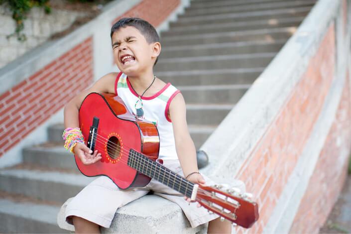 Portfolio enfant Marseille. Enfant entrain de jouer de la guitare.