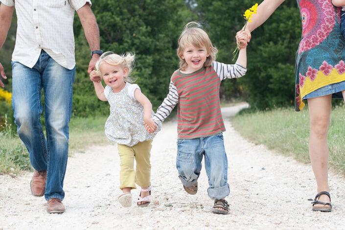 Portrait dynamique de deux frère et sœur marchant sur un chemin de campagne.