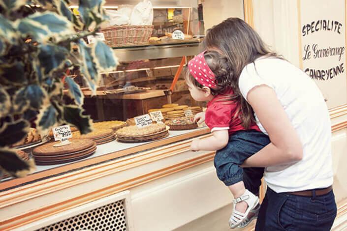 Portrait enfant devant une vitrine de pâtisseries.